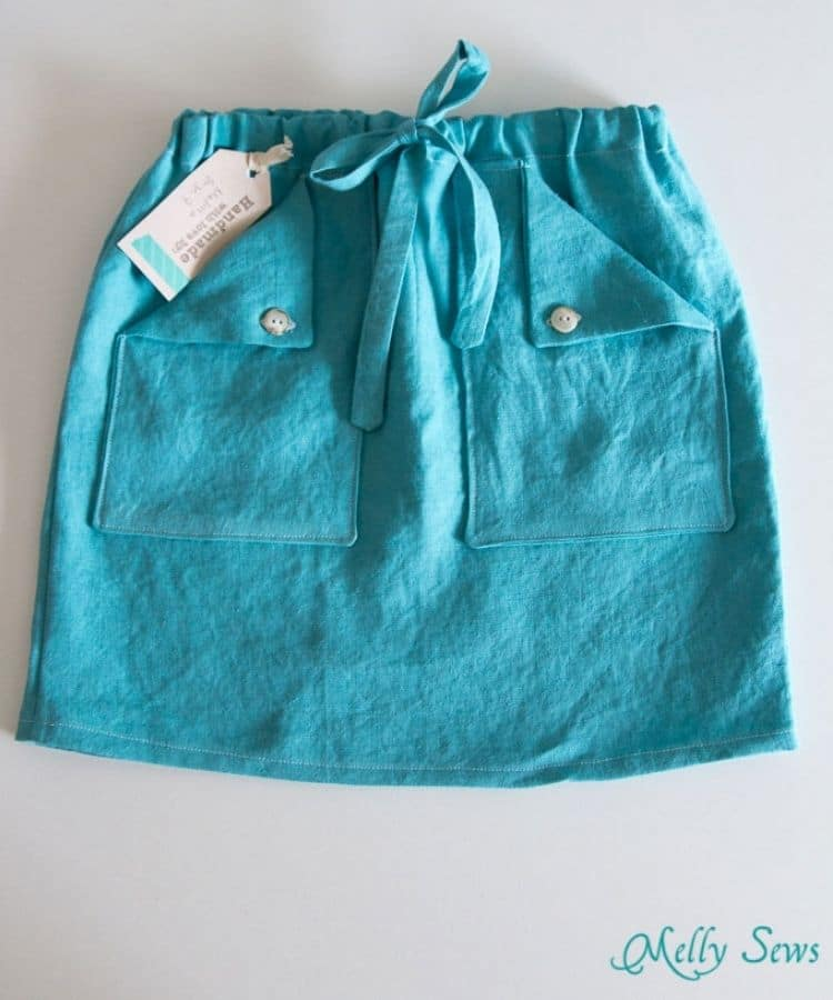 teal linen skirt with drawstring waist and foldover buttoned down pockets laying flat on white background
