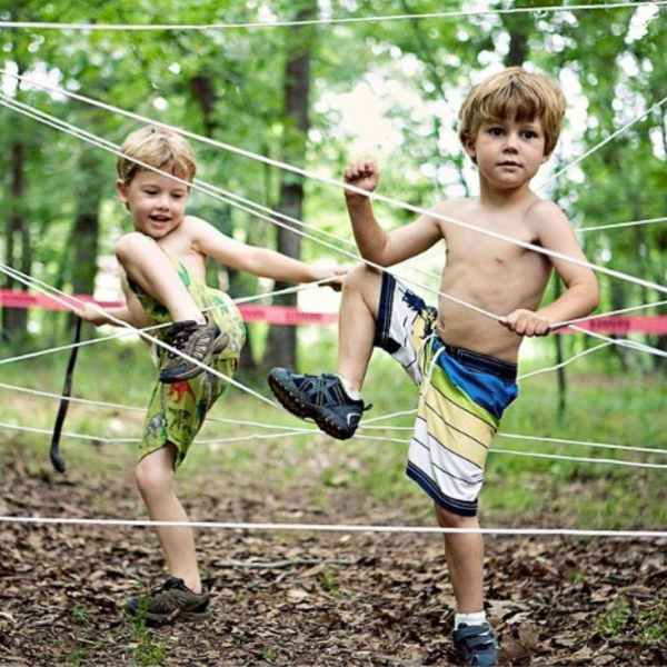 shirtless little preschool boys navigating ropes obstacle course
