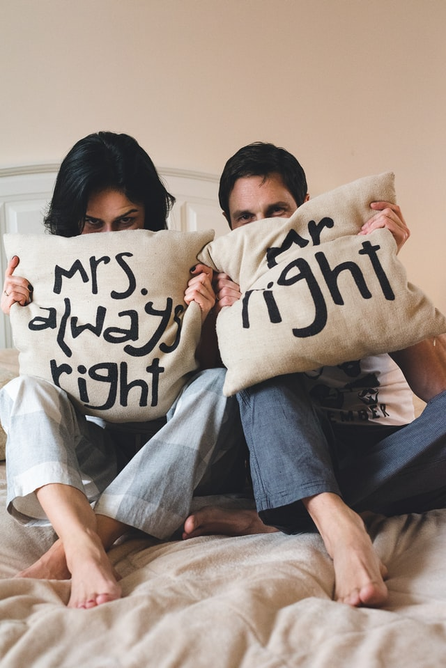 mrs always right pillow held by two people on a bed