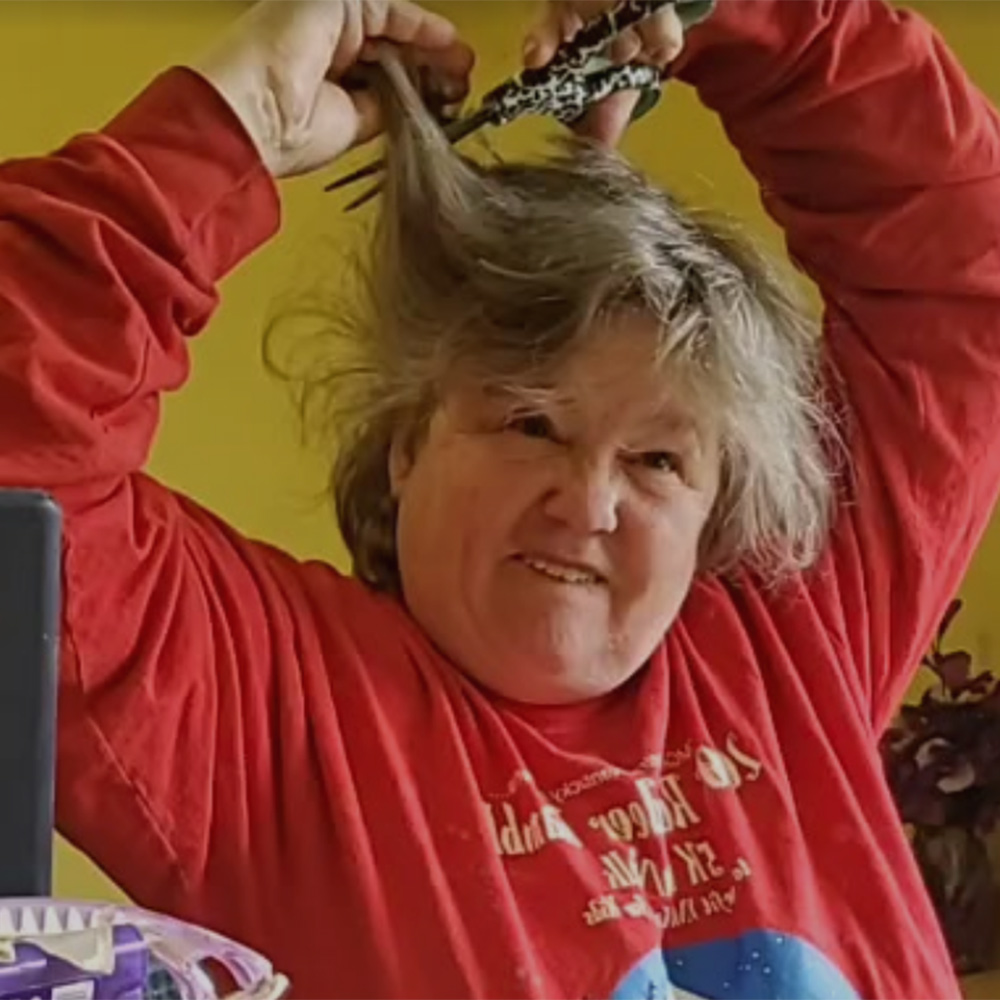 woman makes funny face while cutting her hair