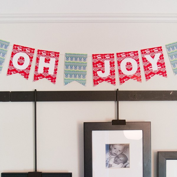 """oh joy"" christmas bunting on wall above photo frames"