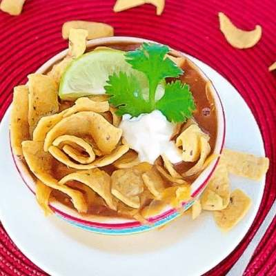red background, round white plate, red striped bowl full of taco soup and fritos