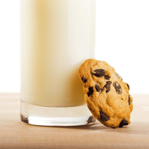 one cookie leaning against a glass of milk