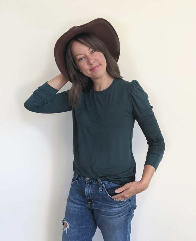 women in brown hat and green long sleeve puffed sleeve shirt