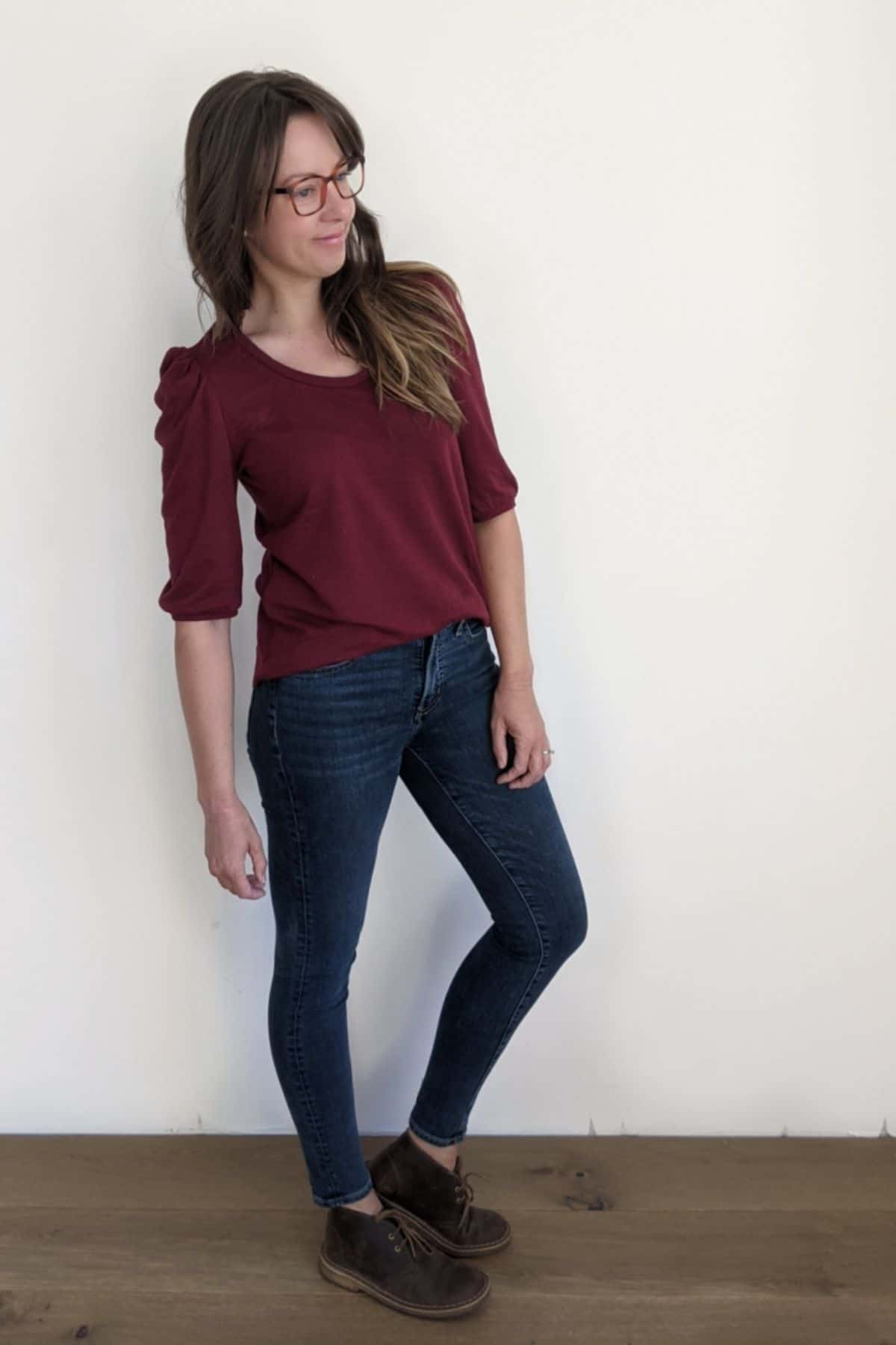 woman stands on wood floor against a white wall. She's wearing skinny blue jeans and a burgundy t-shirt with banded half sleeve puffy sleeves