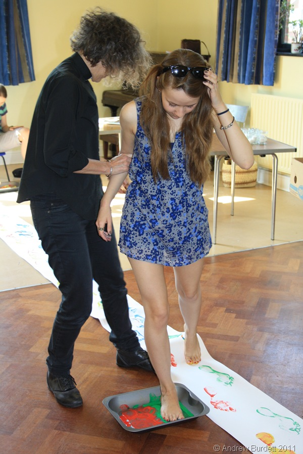 GET STUCK IN_Ruth Baughan, 19, adds her footprints to a path of painted feet.
