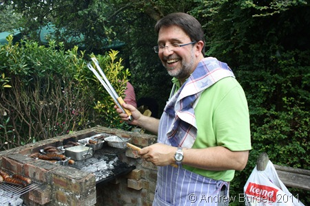 LICENSED TO GRILL_Kevin Baughan, dressed somewhat less formally than during my work experience week, cooks the meat on the barbecue.
