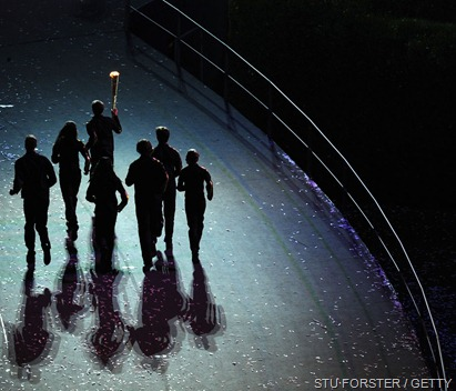 ONE LAST LAP OF HONOUR: The seven young athletes carry the Torch on its final trip - around the Stadium.