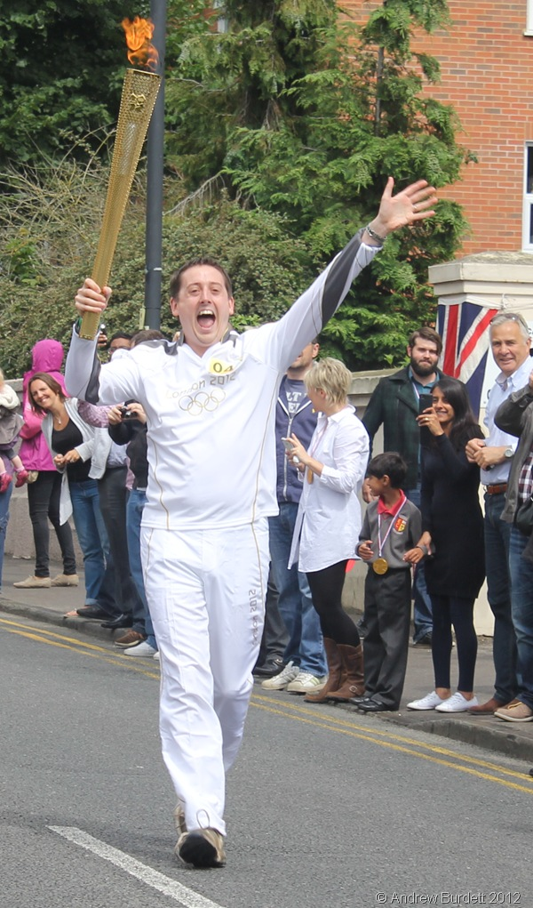 WHAT AN HONOUR: Torchbearer 040 carries the Torch high in the air. (IMG_8875_ARB)