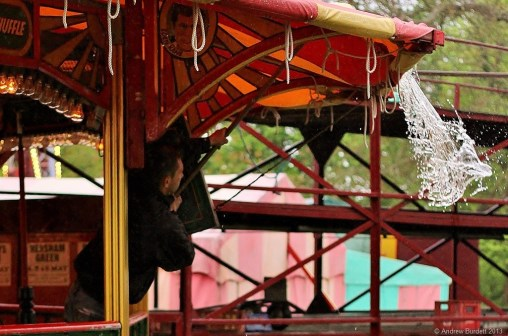 WHAT A DRIP: A Dodgems ride worker empties water off the tarpaulin roof.