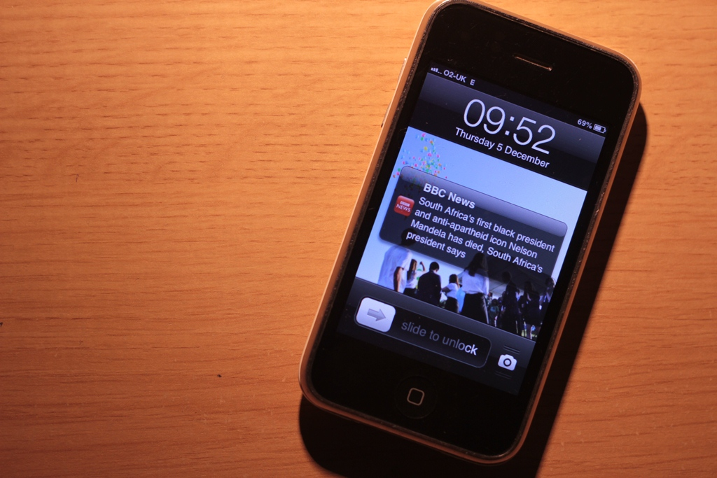 An iPhone with a push notification of Nelson Mandela's death.