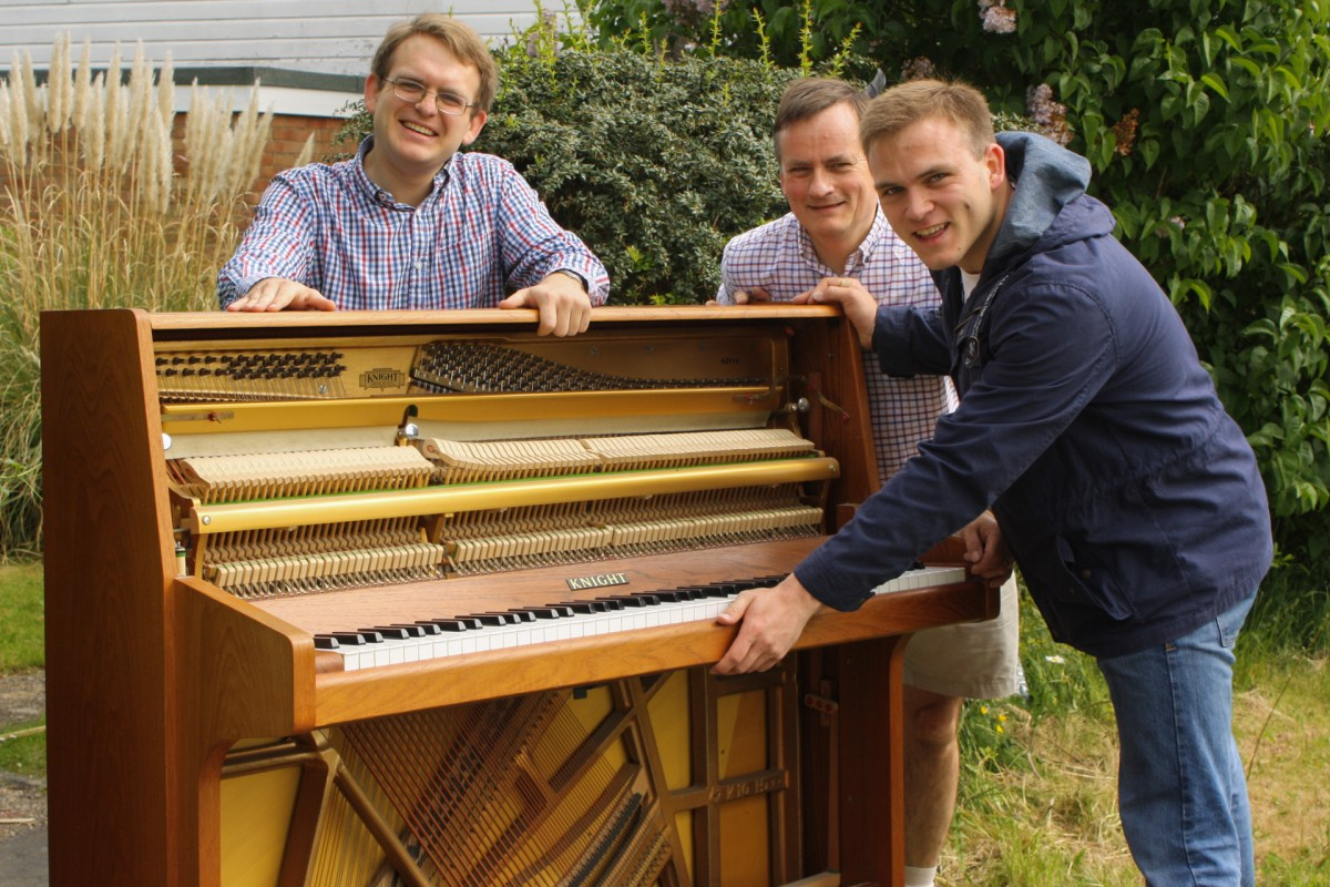 Matthew, Richard, and Andrew Burdett smile for the camera, during the piano move.