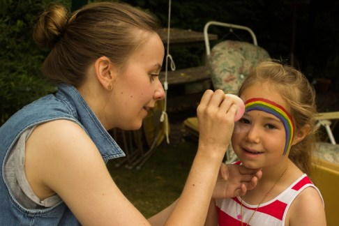 Ruth Baughan paints a rainbow on Charlotte's face.