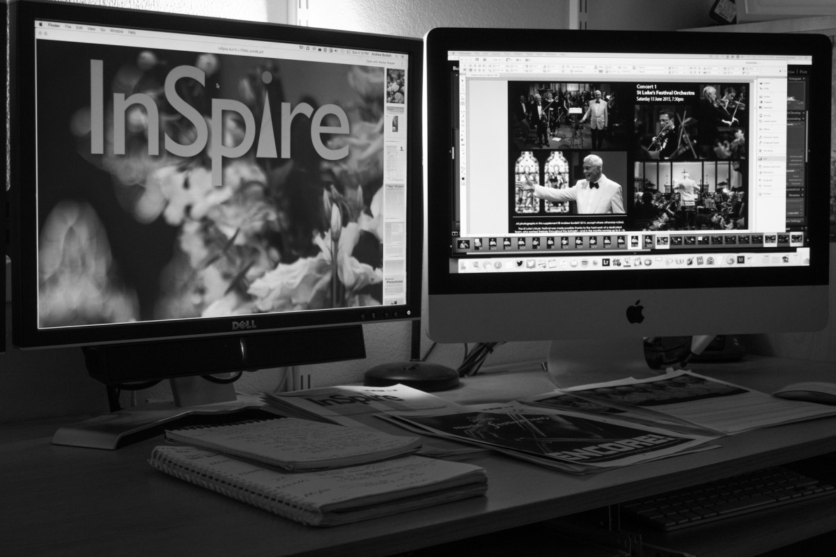 Andrew Burdett's desk with computers displaying an early edition of the Autumn 2015 edition of InSpire.