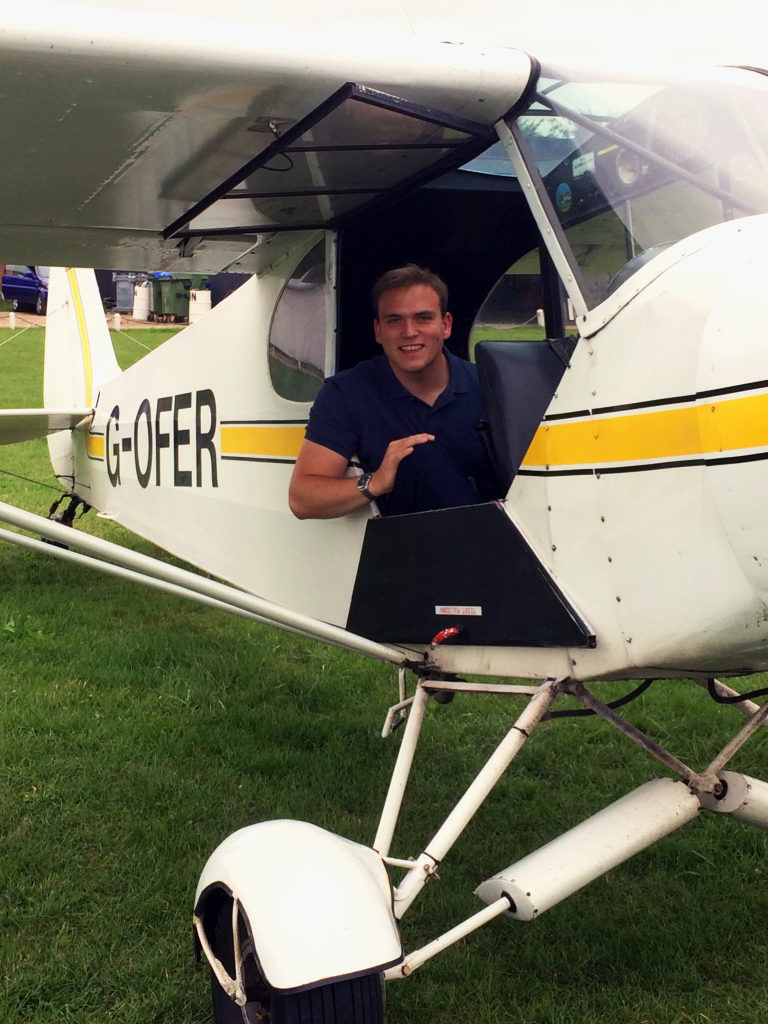 Andrew Burdett sat in the passenger seat of a PA-18 150 Super Cub at White Waltham Airfield.