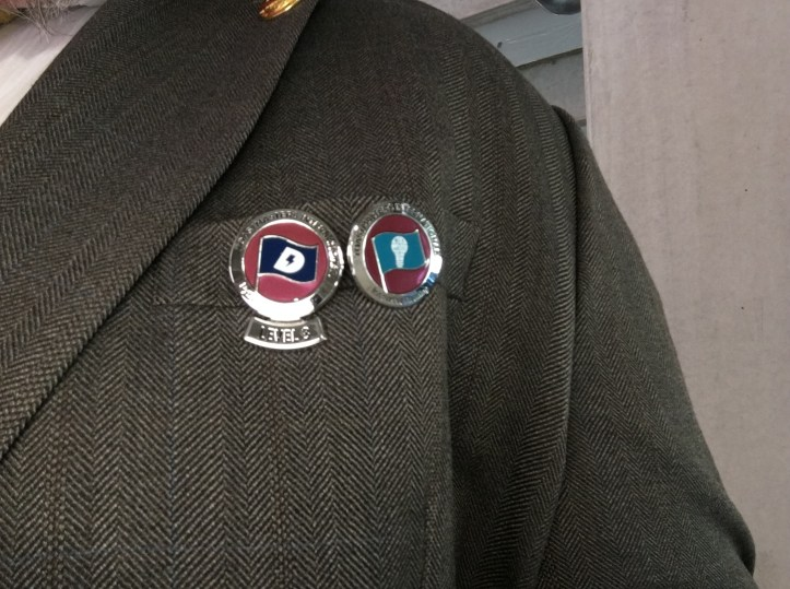 A suit jacket with two prominent pins from toastmasters international