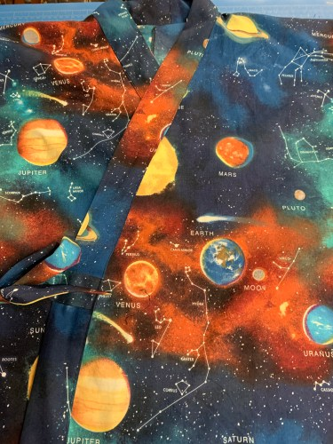 Detail of pattern of fabric, a 100% Joann Fabric cotton showing planets and a star-field.