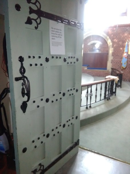 Door from choir vestrey to chancel, in 2017, St Aldhelm's church (W. D. Caroe, 1903)