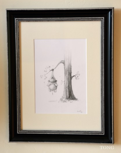 Framed pencil drawing of dwarf elephant hanging on a tree branch using his trunk