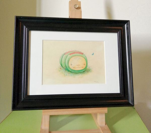 framed drawing on easle showing a green smiling caterpillar