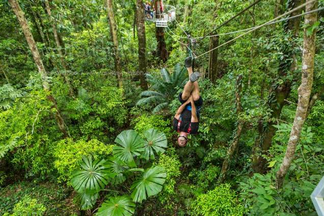 Tourist upside down on zip-line above tropical rainforest