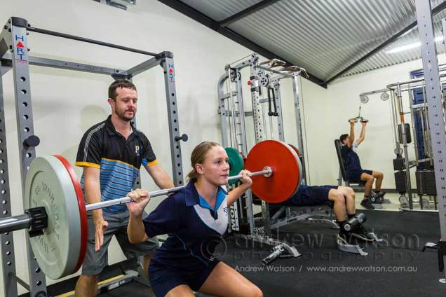 Image of female student lifting weights in the gym