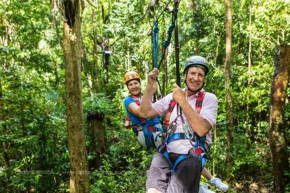Older couple ziplining through rainforest canopy