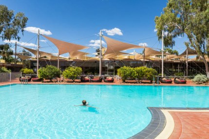 Image of guest swimming in the outdoor pool at Sails in the Desert Hotel