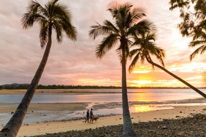Image of couple walking along beach at sunset in Eimeo, Mackay