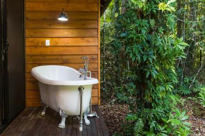 An outdoor bathtub on the deck of a holiday cottage with rainforest beyond