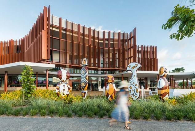 Blurred movement of people walking past indigenous sculptures at Cairns Performing Arts Centre