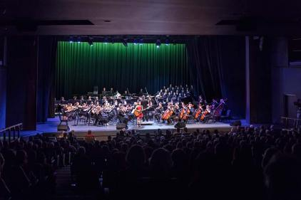 Singer and orchestra on stage during performance at the Cairns Performing Arts Centre