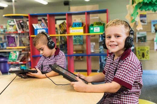 Young student using an iPad and headphones smiling to camera
