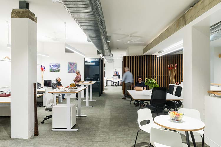 Workers in a busy office space at Bulmba-ja Arts, Cairns