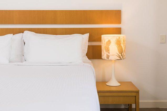 Hotel bed and bedside lamp at Port Douglas resort