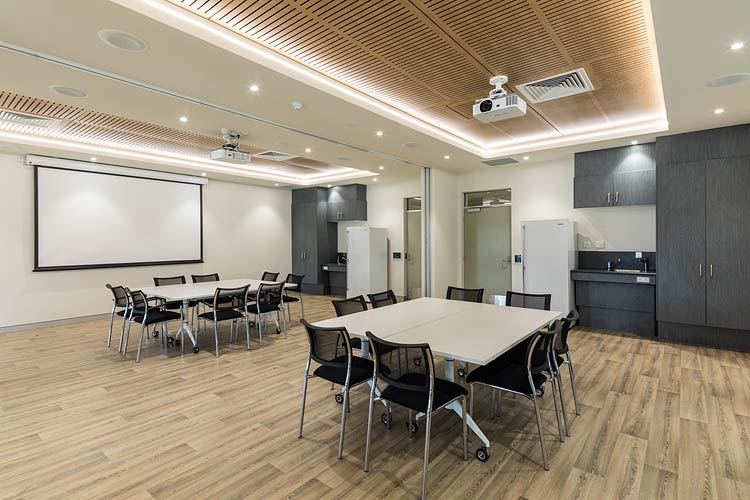Meeting room featuring tables and projector screen