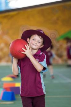 Portrait of young school student holding sports ball