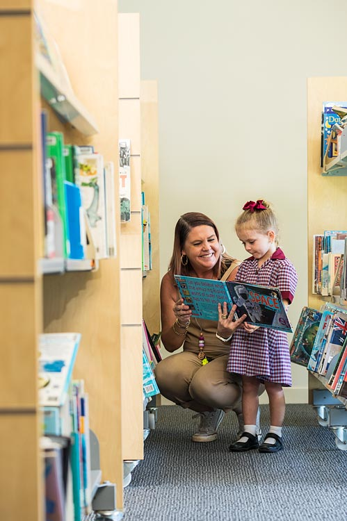 A teacher helping a young student reading in the library