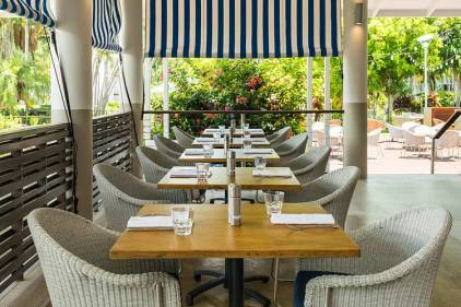Restaurant tables and chairs with view to tropical surrounds