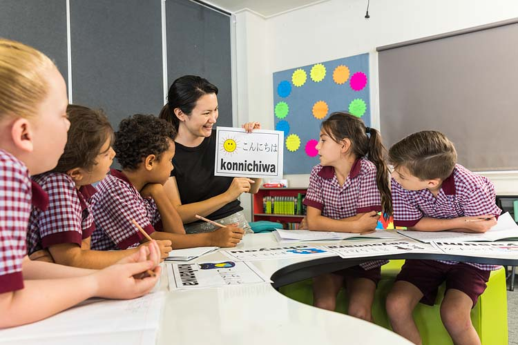 A teacher using language cards to assist students learning Japanese