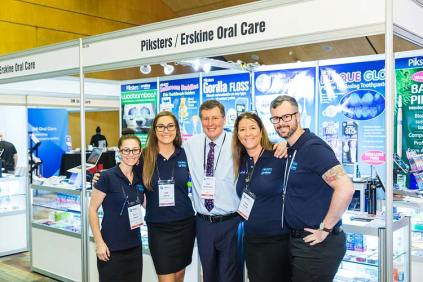 Dental suppliers standing in front of booth at conference tradeshow