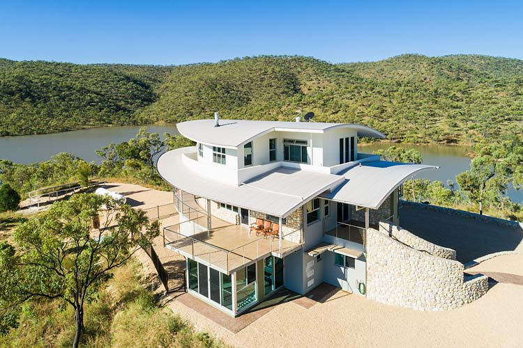 Aerial view of the Walsh River House showing the property's man-made lake and surrounding savannah bushland