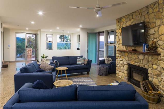 Interior of the Walsh River House showing living area with feature stone wall and fireplace
