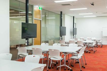 Interior of the James Cook University library showing collaborative learning space tables and screens