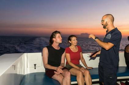A Master Reef Guide talking to two passengers about the spawning dive on the deck of a dive vessel
