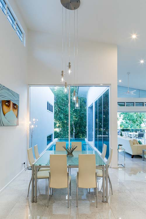 Residential home interior with view of dining area and cantilevered lap pool