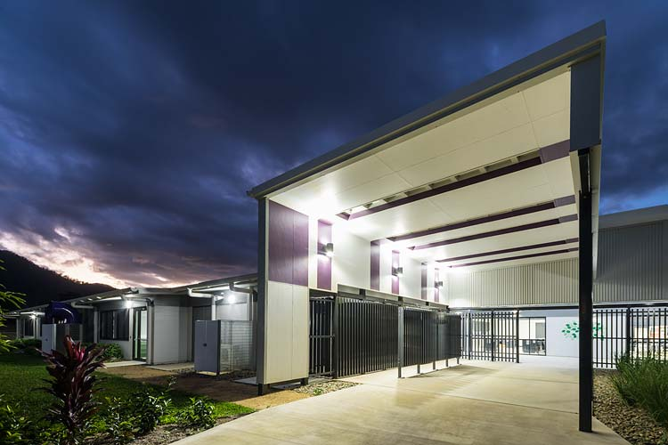 Exterior of new school building with angled roofline over entrance illuminated at twilight