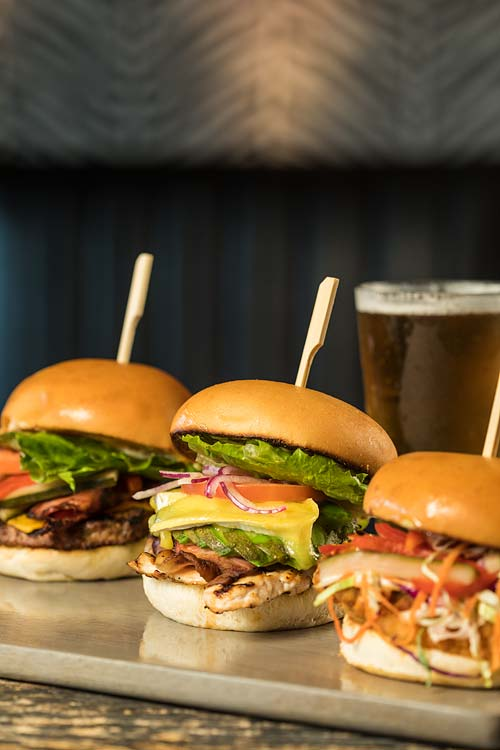 A selection of beef and chicken burgers served with beer