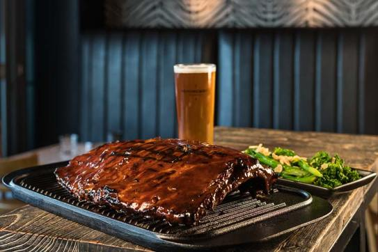 A dish or barbequed pork ribs rack, beer and sides