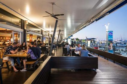 Diners on the open deck of a restaurant overlooking the marina
